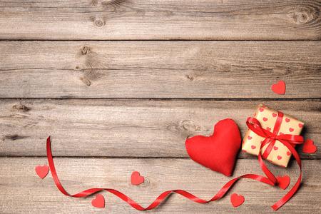 Foto de Heart and gift box with red ribbon on wooden background - Imagen libre de derechos