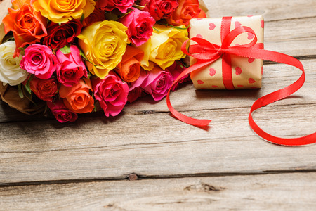 Photo pour Bunch of roses with a gift box on weathered wooden background - image libre de droit