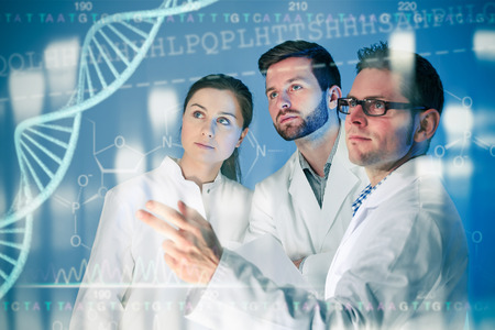 Foto de Group of geneticists working at media screen. Genetic engineering - Imagen libre de derechos