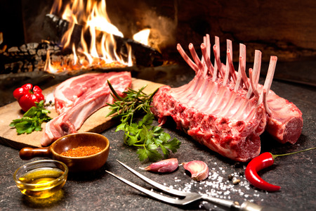 Photo pour Rack of lamb with seasoning in front of a fireplace - image libre de droit