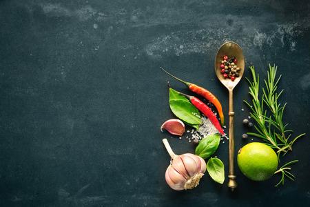 Foto de Herbs and spices with old metal spoon on slate background - Imagen libre de derechos