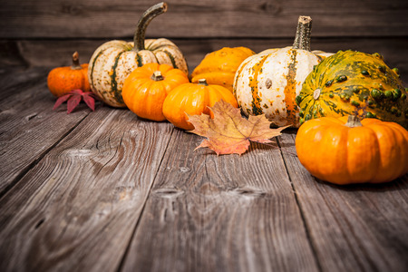 Foto de Autumn still life with pumpkins and leaves on old wooden background - Imagen libre de derechos