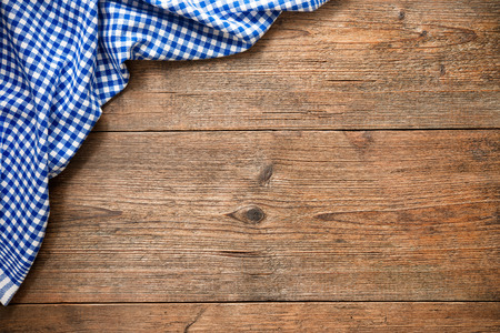 Photo pour Blue checkered tablecloth on wooden table - image libre de droit