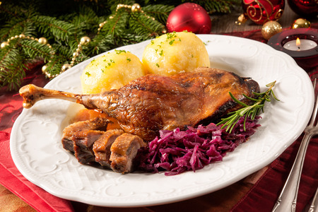 Photo for Crusty goose leg with braised red cabbage and dumplings on Christmas decorated table - Royalty Free Image