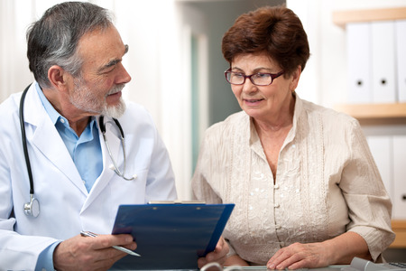 Photo for Doctor talking to his female senior patient at the office - Royalty Free Image