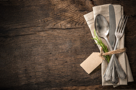 Photo pour Vintage silverware with a twig of rosemary and empty tag on rustic wooden background - image libre de droit