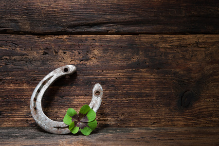 Photo for St. Patricks day, lucky charms. Four leaved clover and a horseshoe on wooden board - Royalty Free Image