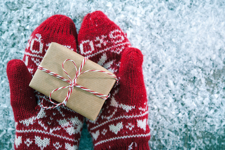 Photo for Female hands in winter gloves with christmas gift box - Royalty Free Image