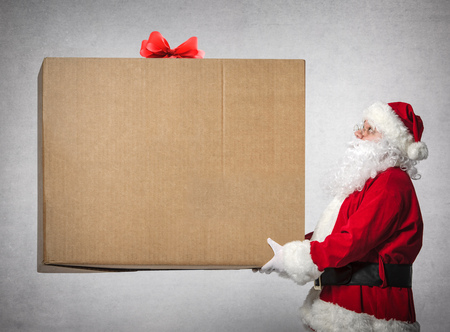 Photo for Santa Claus holds a big gift box with copyspace for your text - Royalty Free Image