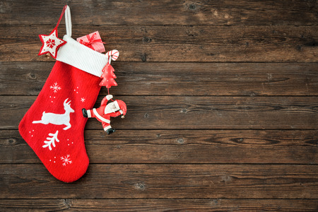Photo for Christmas decoration stocking and toys hanging over rustic wooden background - Royalty Free Image