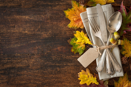 Photo pour Thanksgiving autumn place setting with cutlery and arrangement of colorful fall leaves - image libre de droit