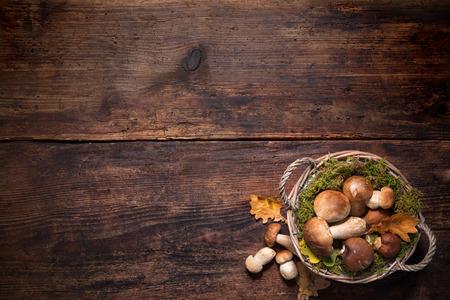 Photo pour Boletus mushrooms in a basket on wooden surface - image libre de droit