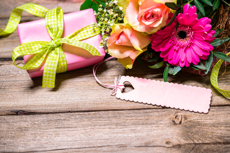 Photo for Background with bouquet of flowers, gift box and an empty tag on wooden board - Royalty Free Image