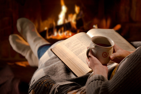Photo pour Woman resting with cup of hot drink and book near fireplace - image libre de droit