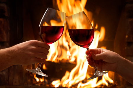 Foto de Hands toasting wine glasses in front of lit fireplace - Imagen libre de derechos