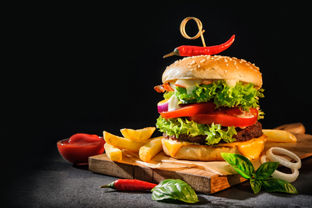 Photo for Delicious hamburgers with french fries on dark background - Royalty Free Image
