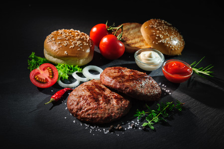 Photo pour Homemade hamburger. Grilled beef patties, sesame buns with other ingredients for hamburgers on dark slate plate - image libre de droit