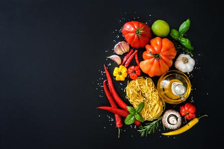 Foto de Italian cuisine. Vegetables, oil, spices and pasta on dark background - Imagen libre de derechos