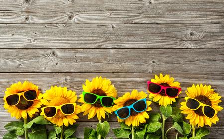 Foto de Sunflowers with sunglasses on wooden board - Imagen libre de derechos