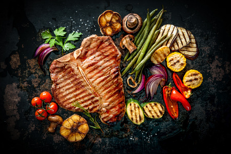 Photo pour Beef T-Bone steak with grilled vegetables and seasoning on dark background - image libre de droit