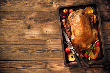 Photo for Roast duck with apples and oranges on baking tray. Cooking at Christmas time - Royalty Free Image