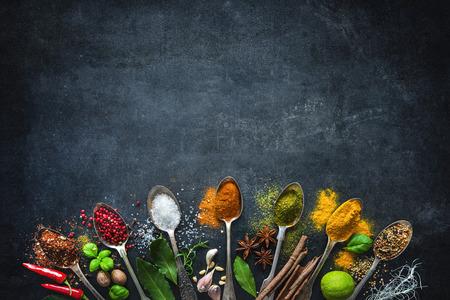 Foto de Various herbs and spices on black stone plate - Imagen libre de derechos