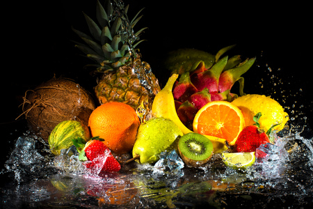 Foto de Fruits on black background with water splash - Imagen libre de derechos
