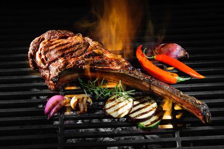 Photo pour Tomahawk rib beef steak on hot black grill with flames - image libre de droit