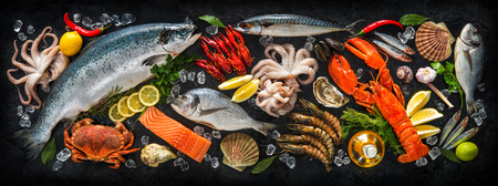 Foto de Fresh fish and seafood arrangement on black stone background - Imagen libre de derechos