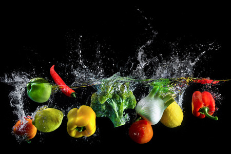 Foto de Vegetables splash in water on black background - Imagen libre de derechos