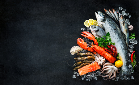 Foto de Fresh fish and seafood arrangement on black stone table - Imagen libre de derechos