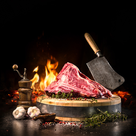 Foto de Raw dry aged t-bone steaks for grill with fresh herbs and cleaver - Imagen libre de derechos