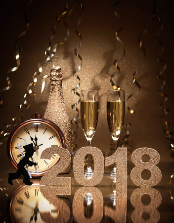 Foto de New Years Eve celebration background with pair of flutes, bottle of champagne, clock and a chimney sweep as lucky charm - Imagen libre de derechos