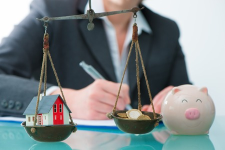 Photo pour Savings or real estate investment concept with house and cash money on scale - image libre de droit