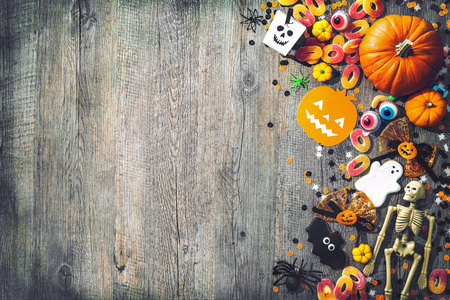 Photo pour Halloween holiday background with skull, skeleton, spiders, pumpkins and candy. View from above - image libre de droit