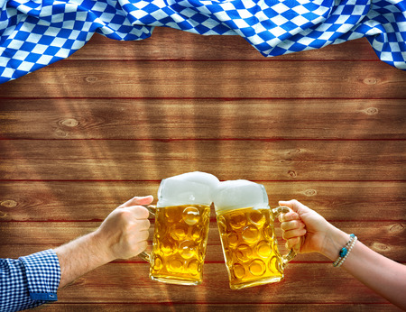Photo pour Cheers! Hands holding up beer mugs under Bavarian flag on wooden background - image libre de droit