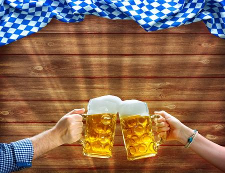 Foto de Cheers! Hands holding up beer mugs under Bavarian flag on wooden background - Imagen libre de derechos