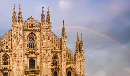 Photo for Facade of Milan, Italys Duomo cathedral with a beautiful rainbow on background - Royalty Free Image
