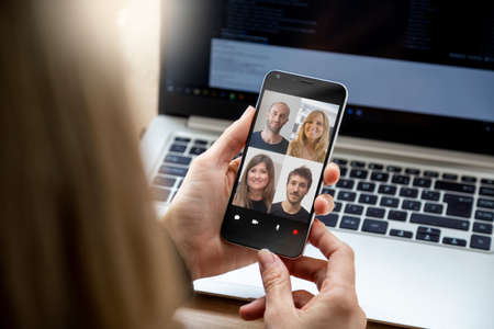 Foto de Woman in video conference with a group of people. Young business woman having a video chat with coworkers on her mobile phone. Woman in her workplace with smartphone in her hands. - Imagen libre de derechos