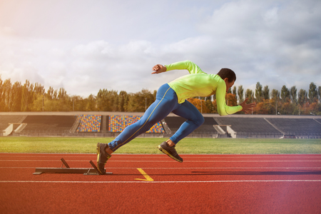 Photo for Afro-American man running around the stadium. Young sprinter on the track for jogging - Royalty Free Image
