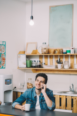 Photo pour Young man relaxing sitting in kitchen and talking on phone with his friends. He is smiling because of having some break. Place for your text or logo - image libre de droit