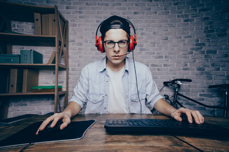 Photo pour Young man playing game at home and streaming playthrough or walkthrough video. Attractive guy in cab and earphones looking at the camera. He seems to be shocked because of vr - image libre de droit