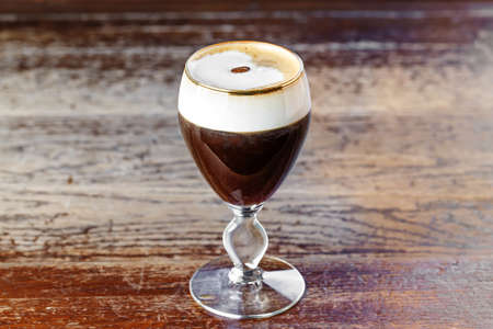 Photo for Irish Coffee is a coffee drink that is classified as a cocktail with cream, based on Irish whiskey, black coffee, whipped cream and brown sugar. - Royalty Free Image