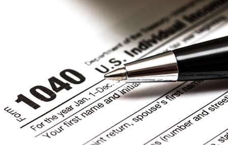 Photo pour US 1040 tax form with pen, and coins - image libre de droit