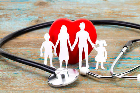 Photo pour Paper silhouette of family, stethoscope and heart on wooden background. Health insurance concept. - image libre de droit