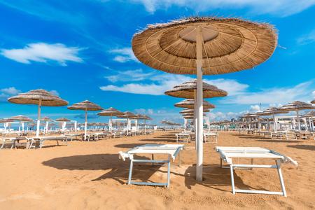 Foto de Straw sun umbrellas on beach. Rimini empty beach with chaise lounges and umbrellas. Clear blue sky background. Summer recreation. Vacation theme. - Imagen libre de derechos