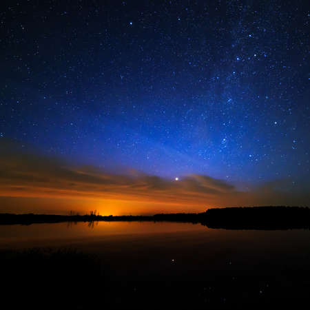 Foto de Morning dawn on a starry background sky reflected in the water of the lake. - Imagen libre de derechos