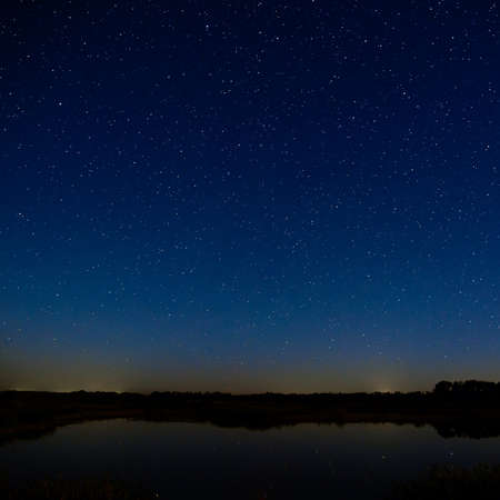 Photo pour The stars in the night sky. Night landscape with a smooth surface of the river. - image libre de droit