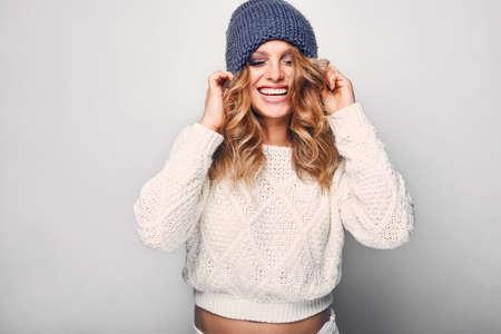 Foto de Portrait of beautiful blond woman in white in white sweater and blue hat - Imagen libre de derechos