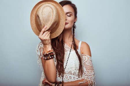 Photo pour Portrait of beautiful young hippie woman wearing hat in studio - image libre de droit